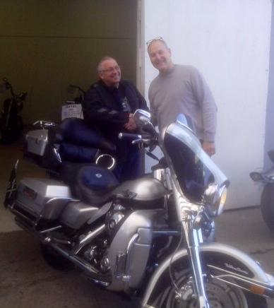 En glad Keld Jensen afhænder en Harley til Claus