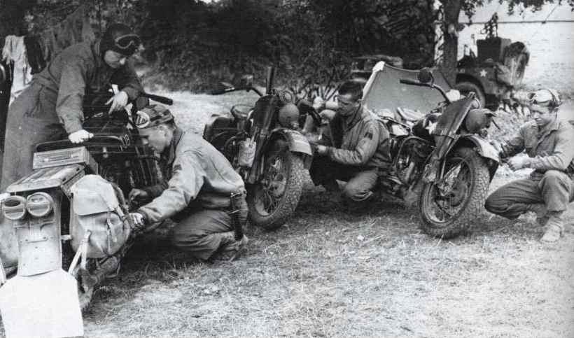 Såkaldte Liberator Riders tilser deres Harleyer på en fransk mark i sommeren 1944